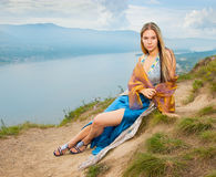 A girl sits on the shore Royalty Free Stock Photos
