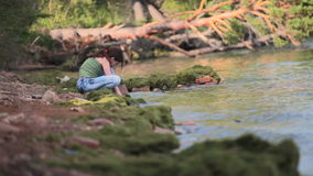 Girl sits on the shore of Baikal. stock footage