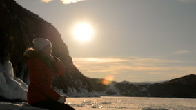 Girl sits on the shore of a frozen lake at sunset. stock video footage