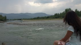 A girl sits on the shore of a mountain river and looks into the distance. Mountains are visible on the horizon.  stock video