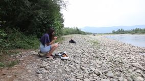 A girl sits on the shore of a mountain river and looks into a smartphone. Nearby travel supplies.  stock video