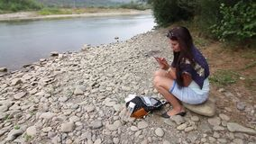 A girl sits on the shore of a mountain river and looks into a smartphone. Nearby travel supplies. The opposite bank of the river. Is visible stock video