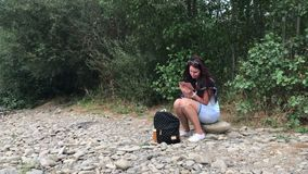 A girl sits on the shore of a mountain river and looks into a smartphone. Nearby travel supplies. The opposite bank of the river. Is visible stock video footage