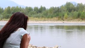 A girl sits on the shore of a mountain river and looks into a smartphone. The opposite bank of the river is visible stock video