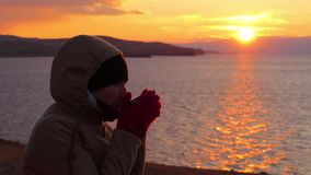 Girl sits on the shore of the sea and drinks a hot tea. Beautiful golden sunset stock video