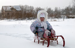Girl sits on sledges Royalty Free Stock Photography