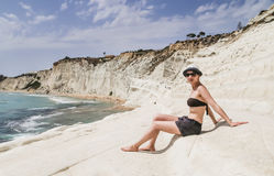 A girl sits on a slope of white cliff called Scala dei Turchi Stock Images