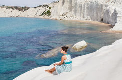 """A girl sits on a slope of white cliff called """"Scala dei Turchi"""" in Sicily Stock Images"""