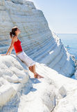 """A girl sits on a slope of white cliff called """"Scala dei Turchi"""" in Sicily, Royalty Free Stock Image"""