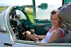 Girl sits and smiles in cabin of old jet fighter MiG-21 holding the control stick Royalty Free Stock Photo
