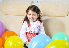 Girl sits on a sofa Royalty Free Stock Photography