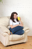 Girl sits on a soft armchair with cup Stock Photo