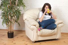girl sits on a soft armchair with cup Stock Photos