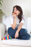 Girl sits on a soft divan eats an apple Stock Images