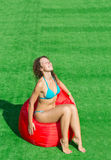 Girl sits on a soft red pufe with eyes closed Royalty Free Stock Images