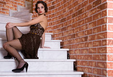The girl sits on the stairs. The posing girl at restaurant in style old-fashioned. she sits down on the stairs Royalty Free Stock Photos