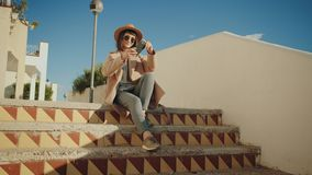 Girl sits on stairs and takes photos on smartphone stock footage