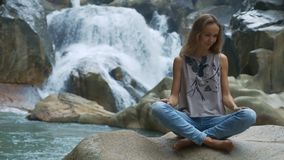 Girl Sits on Stone Enjoys Nature against Waterfall. Closeup beautiful girl in jeans sits on big stone and enjoys nature against small streaming waterfall stock video footage