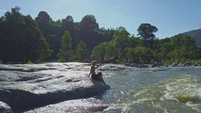 Girl Sits on Stone by River Water Photos Tropical Landscape. Girl sits on large smooth stone in mountain river and takes photos of rapids against tropical plants stock video