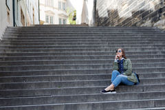 Girl sits on stone steps Stock Image