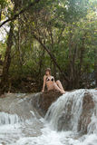 Girl sits on stone in waterfall Royalty Free Stock Photos