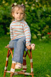 Girl sits on stool. Little girl sits on stool in garden of parents and longs Royalty Free Stock Image