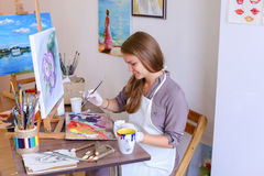 Girl Sits on Stool at Easel And Writing Painting, Uses Brush to Royalty Free Stock Photo