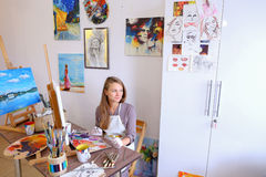 Girl Sits on Stool at Easel And Writing Painting, Uses Brush to Royalty Free Stock Image