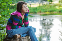 Girl sits on stub Stock Photography