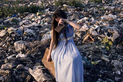 The girl sits on a suitcase with an empty purse among the garbage dump and cries Royalty Free Stock Photography