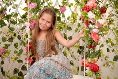 Girl sits on a swing in an arbor. Girl sits on a swing in a flower arbor stock images