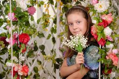 Girl sits on a swing in flower arbor Royalty Free Stock Image