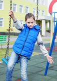 Girl sits on a swing at the playground outdoor Royalty Free Stock Photography