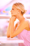 Girl sits at table. Beautiful girl in pink dress sits at table, having leant chin against hands Stock Photography