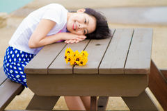 Girl sits on the table with daisy sunflower Royalty Free Stock Photo