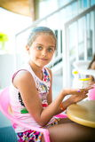 Girl sits at a table and decorates clay figurine Royalty Free Stock Photo