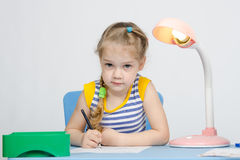 Girl sits at the table and draws a blue pencil Royalty Free Stock Photo