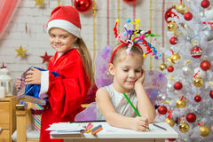 Girl sits at a table with fireworks on the head, Santa Claus brings her Christmas gift Stock Image