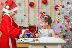 Girl sits at a table with fireworks on the head, Santa Claus gave her a gift Royalty Free Stock Photography