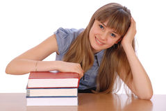 Girl sits at table and has put hands. On a pile of books. On white background Royalty Free Stock Photography