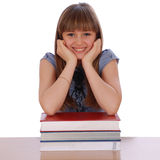 Girl sits  table and has put hands. The girl sits at  table and has put hands on a pile of books. On white background Stock Photography