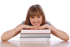 Girl sits at table and has put hands. The girl sits at table and has put hands on a pile of books. On white background Royalty Free Stock Images