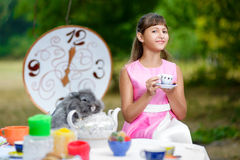 Girl sits at table and holding a cup of tea. Alice Stock Photos