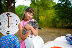 Girl sits at table and holding a rabbit. Alice in Royalty Free Stock Photo
