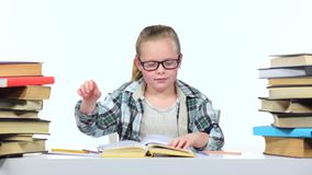 Girl sits at the table leafing through the book. White background stock video footage
