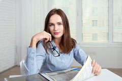 The girl sits at a table in an office holding a newspaper Stock Photos