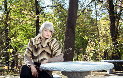 Girl sits at a table in the park. Royalty Free Stock Photo