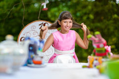 Girl sits at table and pulls her hair. Alice in Royalty Free Stock Photos