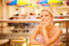 Girl sits at table and smiles Royalty Free Stock Photo