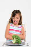 Girl sits at table unhappy with food Stock Photo